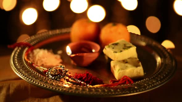 Spinning Puja Thali With Rakhi, Sweets And Oil Lamp